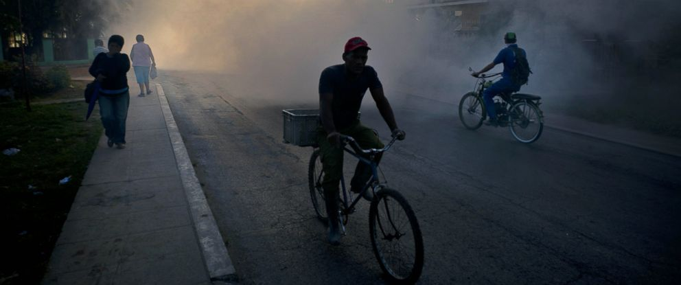 PHOTO: People make their way through fumigation fog, sprayed to kill Aedes Aegypti mosquitos, in Pinar del Rio, Cuba, March 1, 2016.