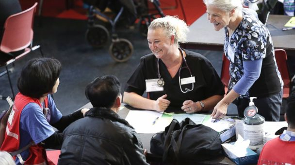 PHOTO: Nursing student Coral Janisse (2R) checks in patients as people get free dental, vision and medical care during the Seattle/King County Clinic at the Key Arena in Seattle, on Oct. 28, 2016.