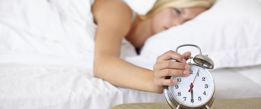 PHOTO: Woman turning off an alarm clock in an undated stock photo.