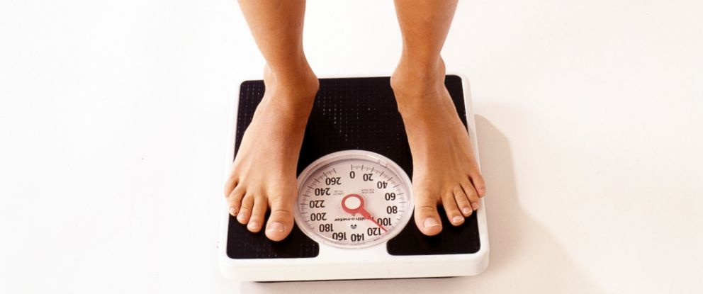PHOTO: A person standing on a scale being weighed.