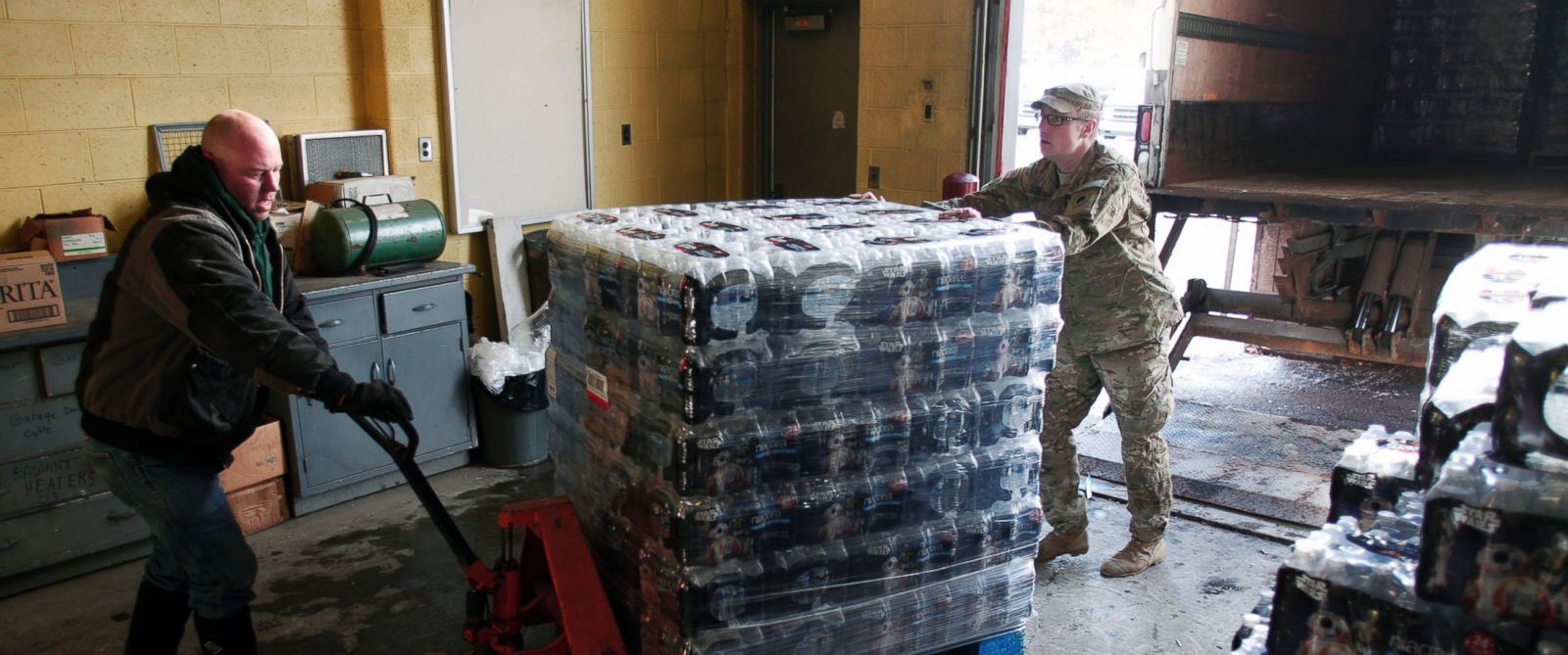Photo: Michigan National Guard Staff Sergeant William Phillips (right),  Helps A Worker