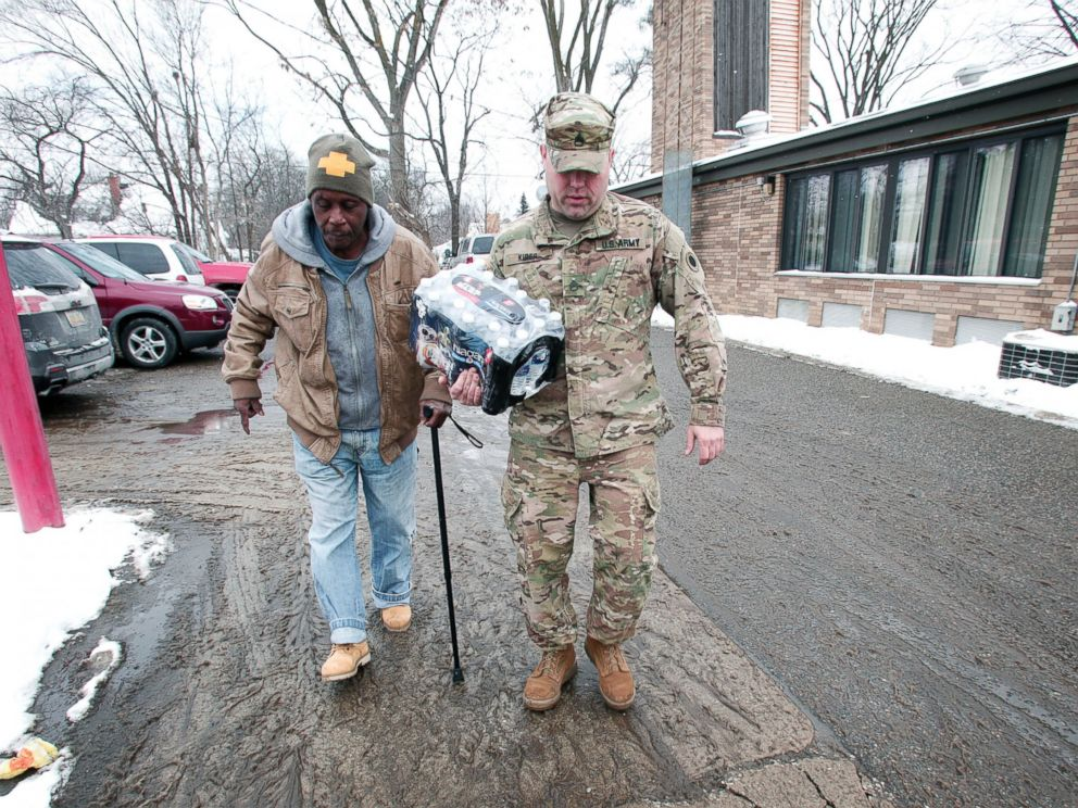 PHOTO: Michigan National Guard Staff Sergeant Steve Kiger helps a Flint resident take bottled water out to his car, Jan. 13, 2016 in Flint, Michigan.