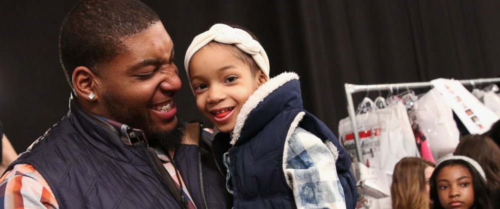 PHOTO: NFL player Devon Still, left, and his daughter prepare backstage at the Nike Levis Kids fashion show during Mercedes-Benz Fashion Week Fall 2015 at The Salon at Lincoln Center, Feb. 12, 2015, in New York.
