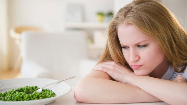 PHOTO: In this stock image, a woman angrily glares at a plate of green peas.