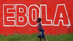 """PHOTO: A girl walks past a painted wall reading """"Stop Ebola"""" in Monrovia, Liberia on Aug. 31, 2014."""