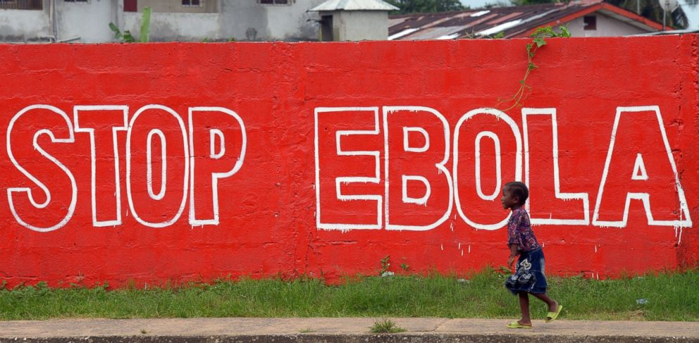PHOTO: A girl walks past a painted wall reading Stop Ebola in Monrovia, Liberia on Aug. 31, 2014.