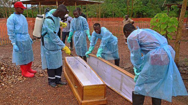 PHOTO: Sierra Leonese government burial team members are pictured wearing protective clothing while disinfecting a coffin at the Medecins Sans Frontieres facility in Kailahun, Sierra Leone on Aug. 14, 2014.