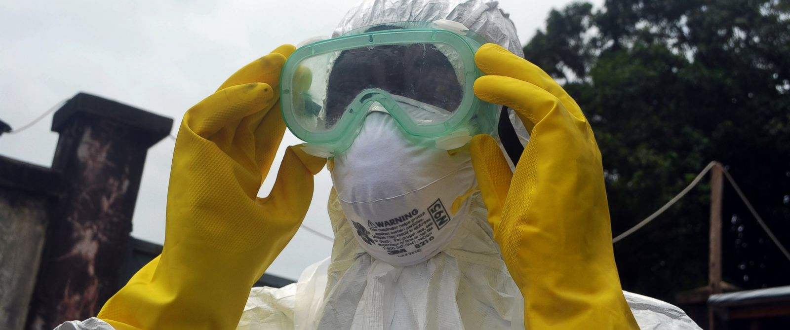 PHOTO: A member of a volunteer medical team wears protective glasses before burying the body of an Ebola victim in Conakry, Guinea on Sept. 13, 2014.