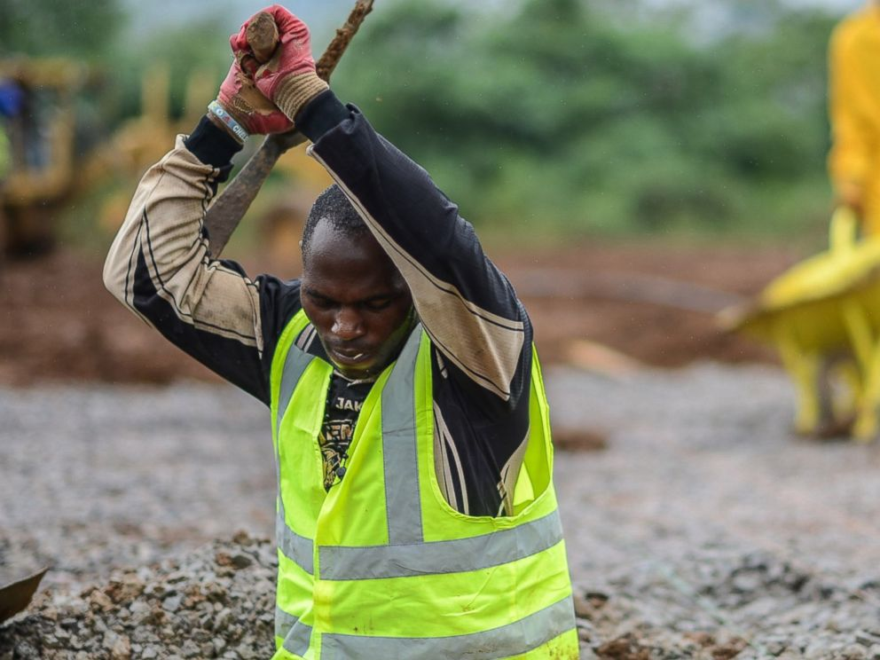 PHOTO: A worker of the International Committee of the Red Cross digs a hole with a pickaxe during the construction a brand new health center in Kenema, Sierra Leone on Aug. 25, 2014.