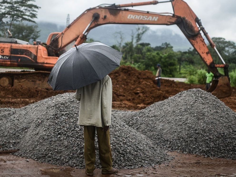 PHOTO: A man with an umbrella watches workers from the International Committee of the Red Cross during the construction a brand new health center in Kenema, Sierra Leone on Aug. 25, 2014.