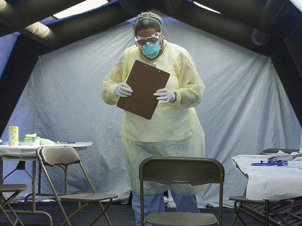 PHOTO: Deddie Craig, a registered nurse at UNC Hospitals, retrieves paperwork from a screening tent at the SARS medical screening facility on June 13, 2003 in Chapel Hill, N.C.