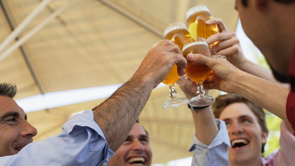 PHOTO: In this stock image, four men are pictured toasting outdoors.