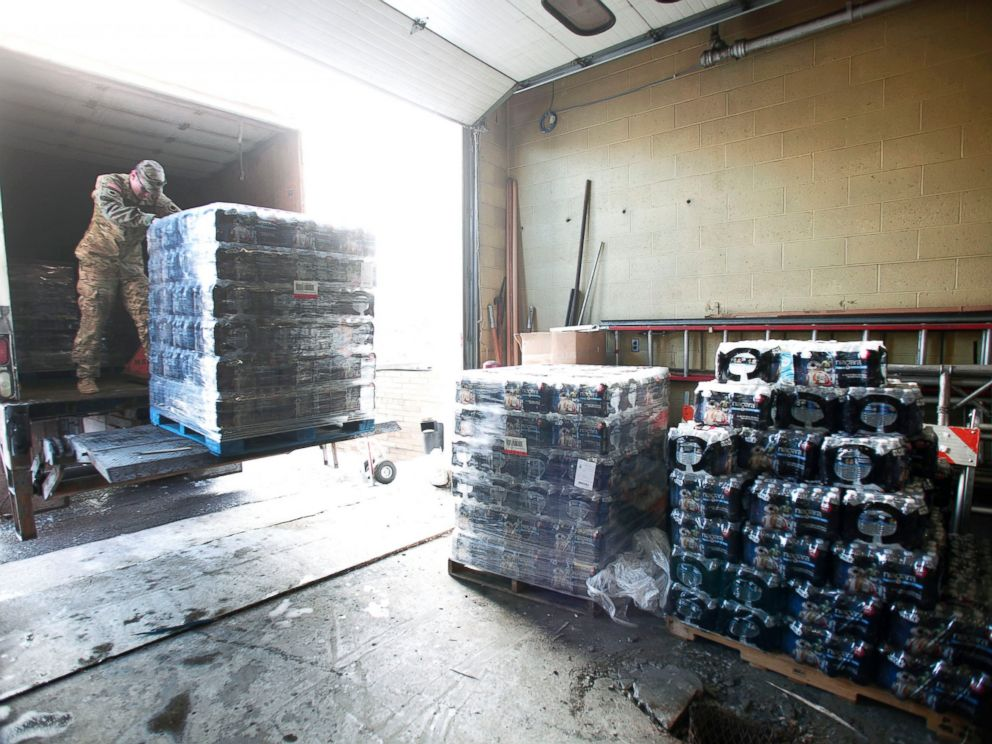 PHOTO: Michigan National Guard Staff Sergeant William Phillips of Birch Run, Michigan, helps unload pallets of bottled water at a Flint Fire Station, Jan. 13, 2016, in Flint, Michigan.