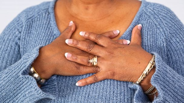 PHOTO: In this stock image, a woman is pictured experiencing possible heart attack symptoms.
