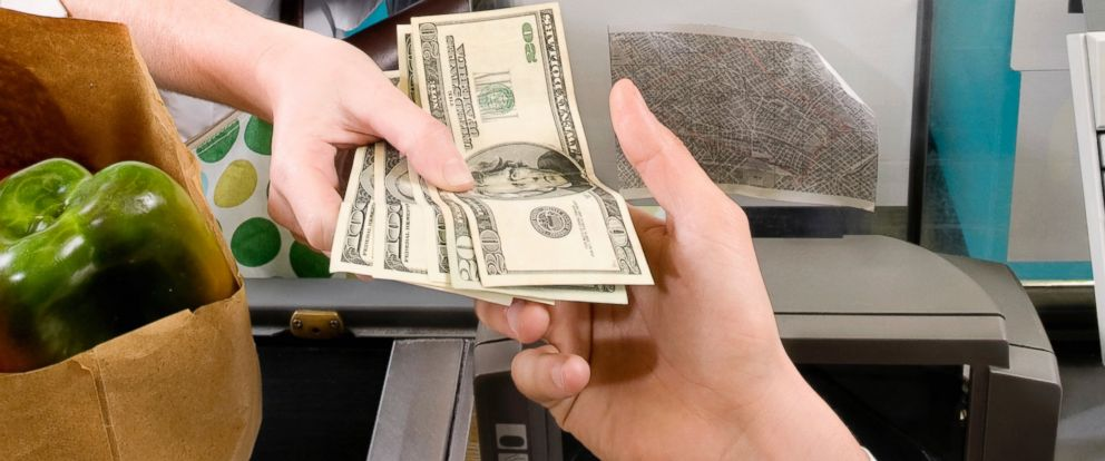 PHOTO: A customer is pictured handing a cashier money in this stock image.