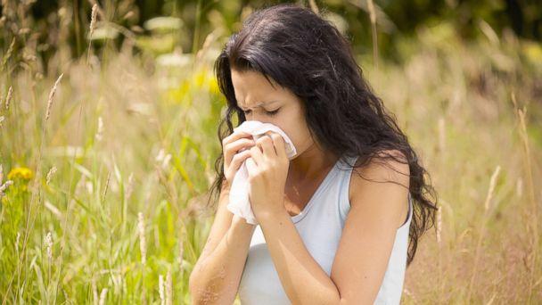 PHOTO: A woman sneezes.