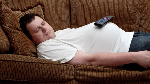 PHOTO: A man sleeps on the couch, with a TV remote control balancing on his protruding stomach.