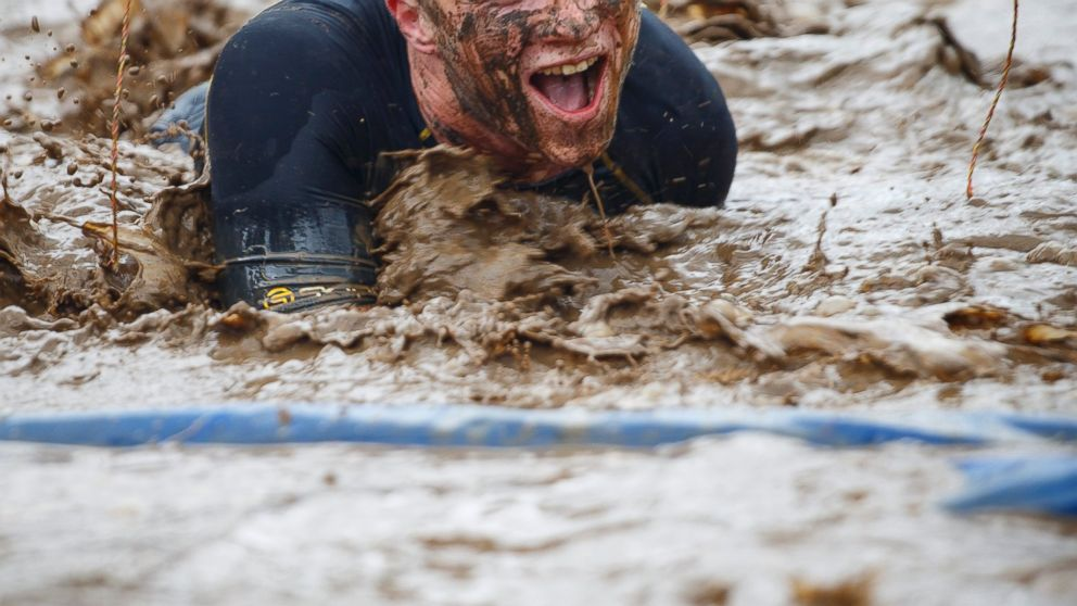 PHOTO: A competitor crawls in mud while competing in the Tough Mudder endurance race in Henley-on-Thames, England on April 27, 2014.