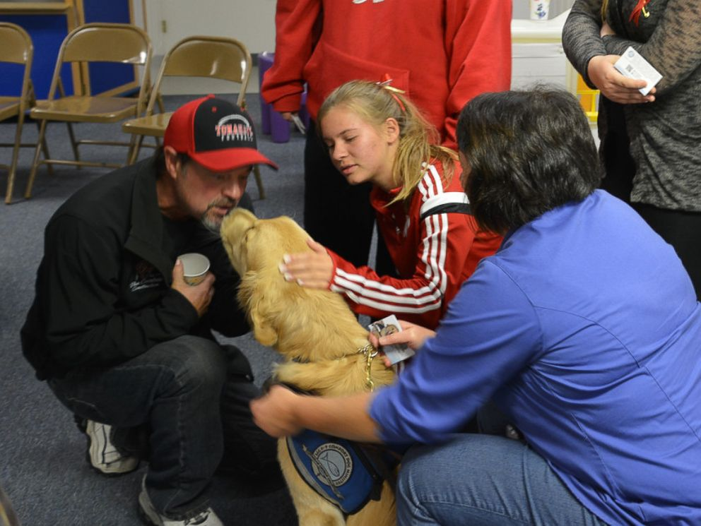 PHOTO: Residents hugged the golden retrievers at a church gathering Monday night.