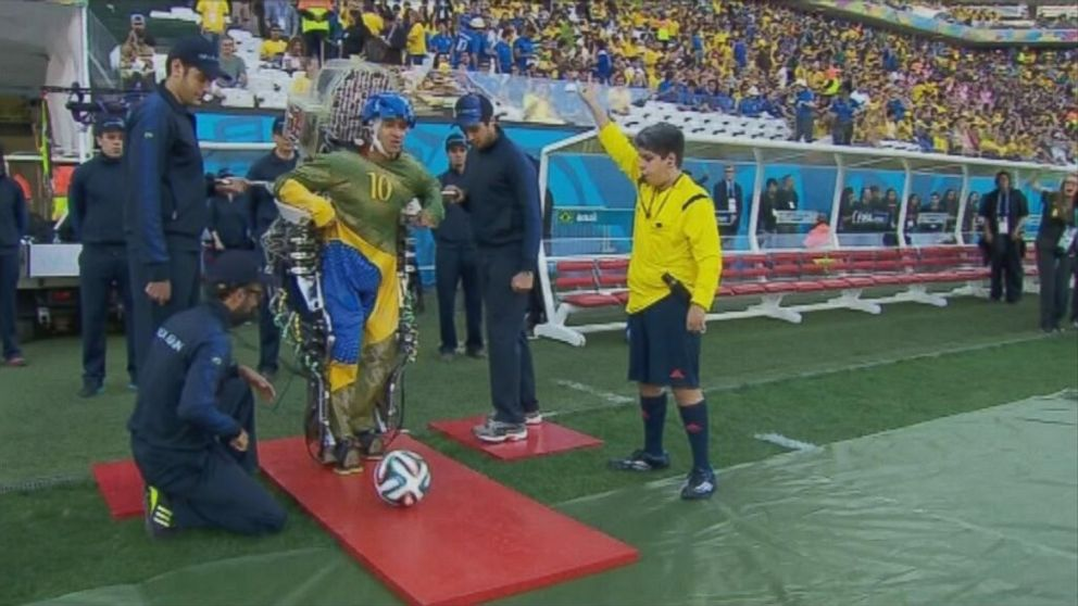 PHOTO: A paraplegic man wears an exoskeleton kicks a soccer ball