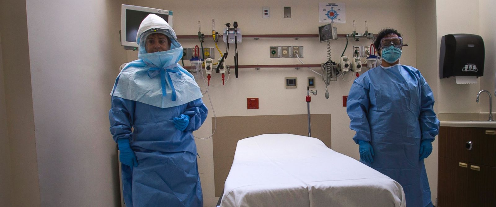 PHOTO: Health care workers display protective gear inside an isolation room as part of a media tour of the emergency department of Bellevue Hospital in New York City, Oct. 8, 2014.