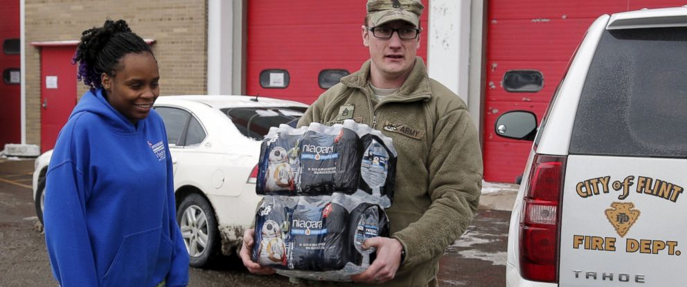 PHOTO: Michigan National Guard Staff Sergeant William Phillips, right, assists a Flint resident with bottled water at a fire station in Flint, Mich., Jan. 13, 2016.