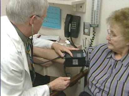 A doctor testing a womans blood pressure.