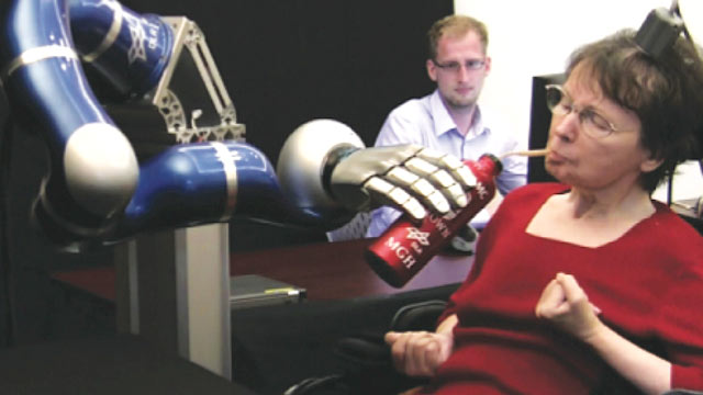 PHOTO: A paralyzed woman uses a mind-controlled robotic arm to drink from a bottle.