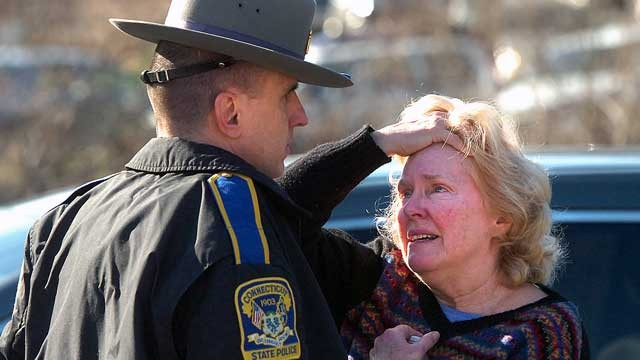 PHOTO: A woman speaks with a Connecticut State Police officer near Sandy Hook Elementary School, Dec. 14, 2012 in Newtown, Conn.