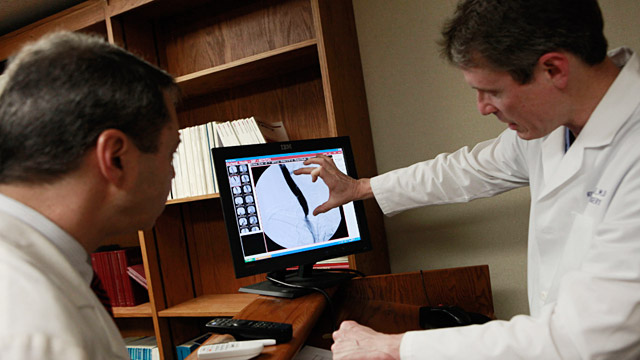 PHOTO: Doctors looking at record of patient with M.S.
