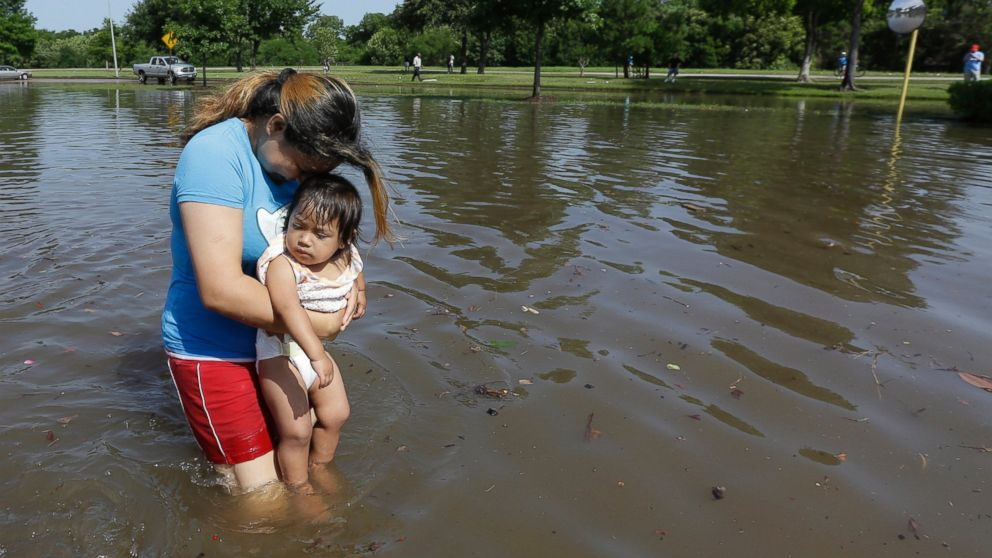 PHOTO: Gabby Aviles carries her daughter Audrey through floodwaters outside their apartment in Houston, May 26, 2015.