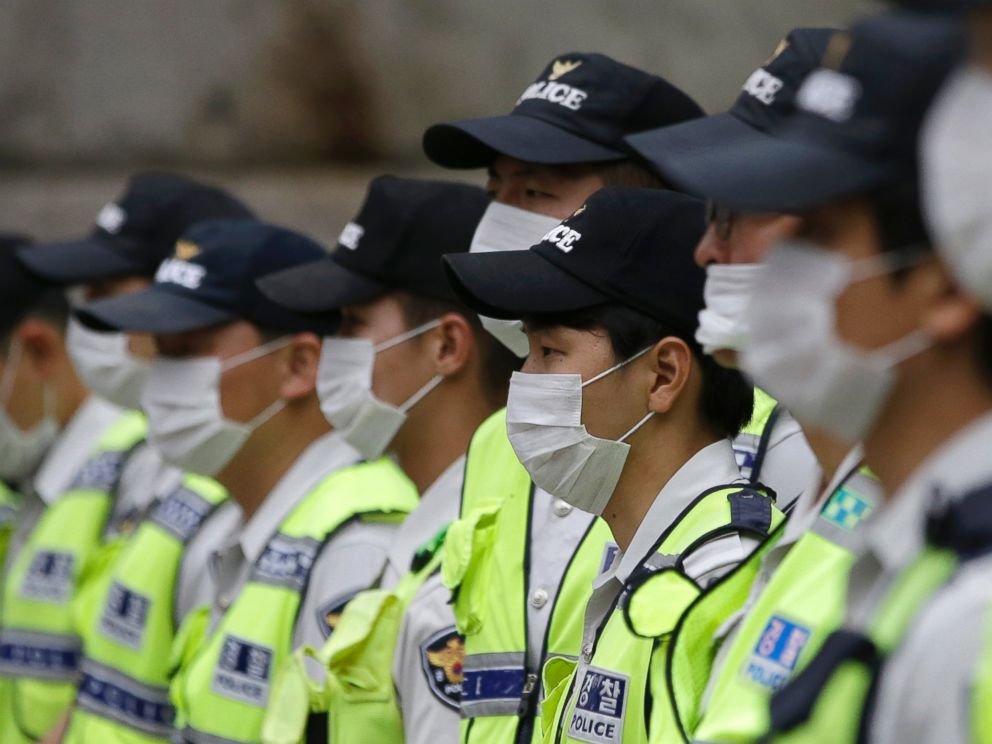 PHOTO: South Korean police officers wearing masks as a precaution against MERS stand guard during a rally in Seoul, South Korea, June 11, 2015.