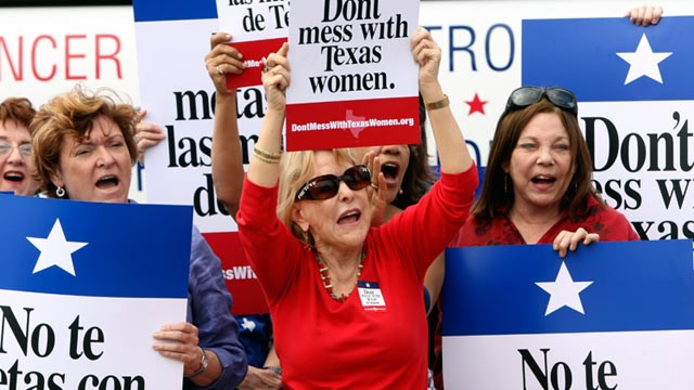 PHOTO: Mary Green, Peg Armstrong and Jan Perrault hold up signs during Women's Health Express, a bus event held in San Antonio, Texas, to protest the attempt to cut Planned Parenthood out of the state's Women's Health Plan, March 6, 2012.