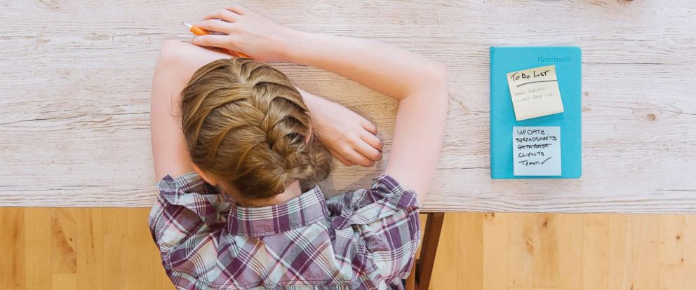 PHOTO: An exhausted woman rests her head on a table in this undated stock photo.