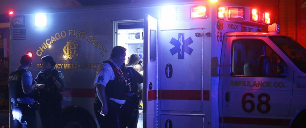 PHOTO: Police officers listen to a woman as paramedics tend to a man in an ambulance, Oct. 2, 2016, in Chicago, Ill.