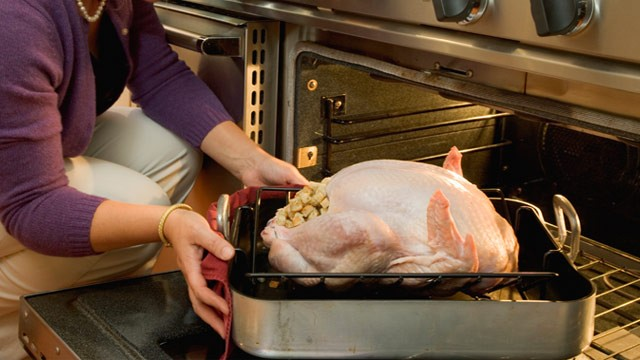 PHOTO: Woman putting stuffed turkey into oven