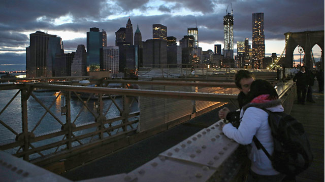 PHOTO: A couple kisses on the Brooklyn Bridge in front of the partially-lit skyline of lower Manhattan after Superstorm Sandy in New York, Nov. 3, 2012.