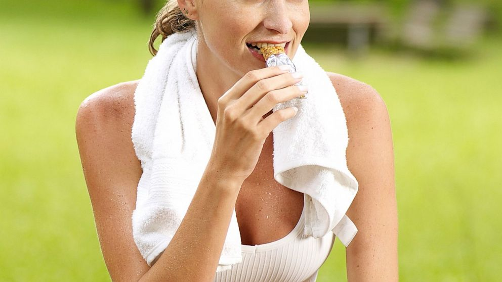 A woman eats a granola bar after exercise.