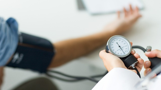 PHOTO: Doctor checking patient's blood pressure
