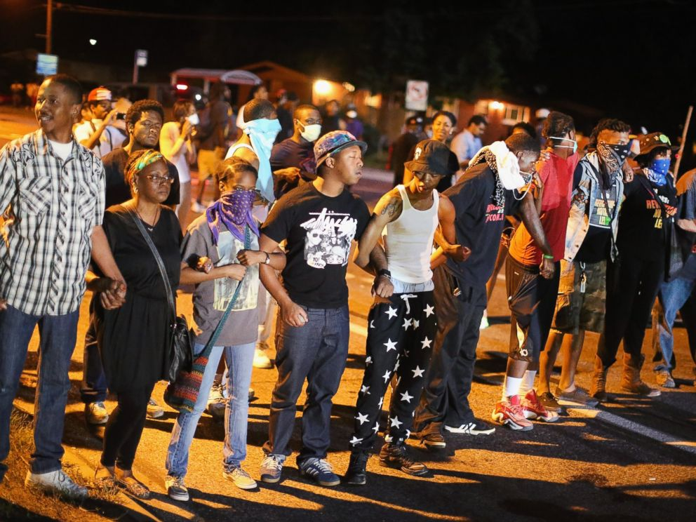 PHOTO: Demonstrators protest the shooting death of teenager Michael Brown on August 13, 2014 in Ferguson, Missouri.
