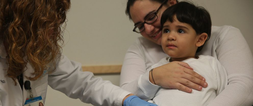 PHOTO: Yasunary Garrido holds her son, Samuel Espinoza, 2, as he receives a flu vaccination from Dr. Amanda Porro M.D. during a visit to the Miami Childrens Hospital on Jan. 7, 2015 in Coral Gables, Fla.