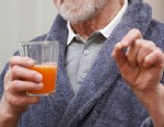PHOTO: Man taking pill with grapefruit juice