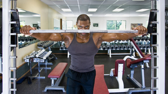 PHOTO: A man stands behind a weight in the gym.