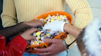 PHOTO: Children in Halloween costumes reaching into bowl of candy.