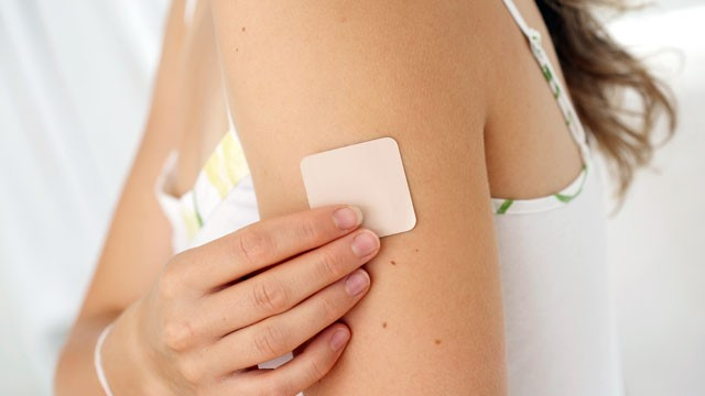 PHOTO: A woman places a nicotine patch on her arm.