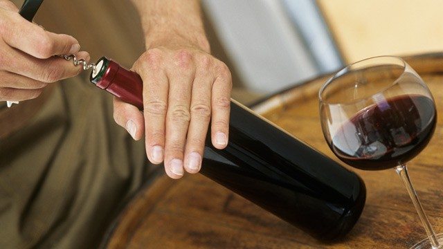 PHOTO: Man opening bottle of red wine