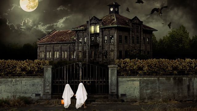 PHOTO: Children in ghost costumes trick or treat at a haunted house.