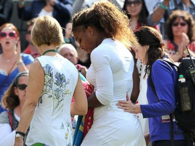 PHOTO: Serena Williams and her sister Venus Williams leave the court after retiring from their womens doubles match after Serena was taken ill during the 2014 Wimbledon Championships in Wimbledon, southwest London, on July 1, 2014.