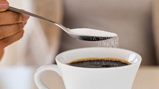 PHOTO: Woman spooning sweetener into coffee