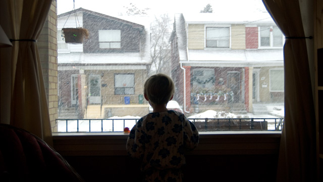 PHOTO: Boy looks out of widow at snow